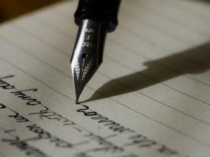 Lähikuva mustekynästä, joka kirjoittaa paperille kaunoa.