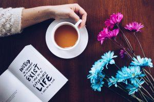 Pöydällä kahvikuppi, kirja, kukkia.