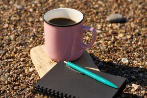 Maassa kahvikuppi sekä muistiinpanovihko ja kynä.