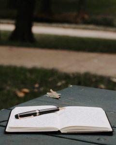 Avoin tyhjä vihko ja kynä penkin päällä. Taustalla kävelytie ja puistomaisema.