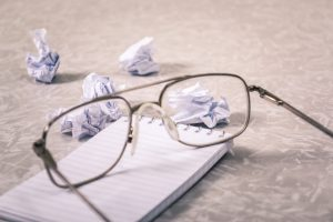 Silmälasit tyhjän vihon päällä, taustalla rutattuja paperikasoja.