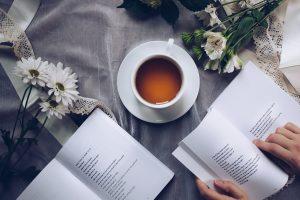Pöydällä kukkia, kahvikuppi sekä kirjoja.