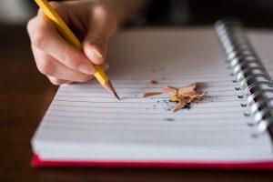 Henkilö kirjoittaa paperille lyijykynällä, paperin päällä on kynän teroitttamisesta jääneitä roskia.