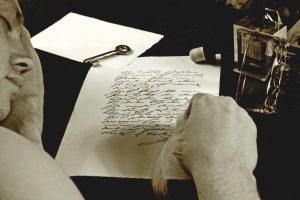Henkilö kirjoittaa pöydän äärellä sulkakynällä.